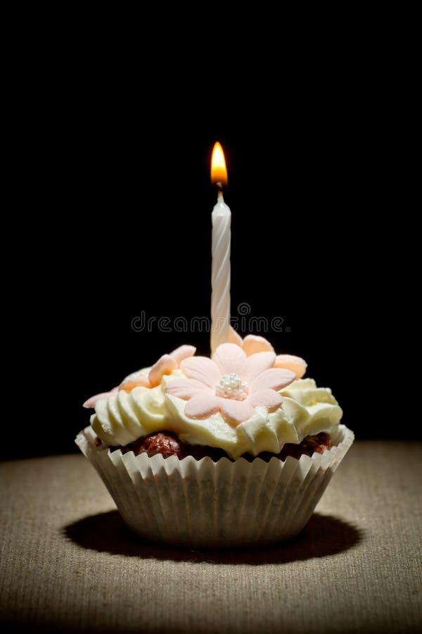 De muffin van de verjaardag met kleine brandende kaars stock afbeeldingen