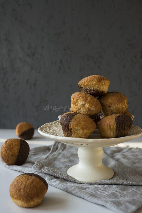 De muffins van de vanillechocolade op ceramische caketribune Grijze achtergrond en ruimte voor tekst royalty-vrije stock fotografie