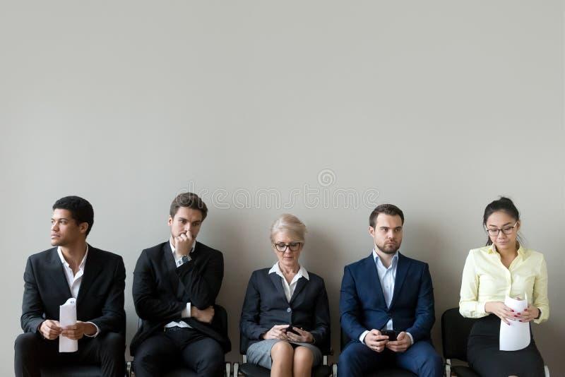 De multi-etnische kandidaten die in rij zitten vormen lijn een rij voorbereidingen treffend voor gesprek royalty-vrije stock afbeeldingen