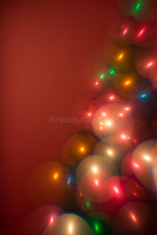 De multiboom van kleurenkerstmis steekt bokeh aan als bellen op een rode achtergrond stock foto's