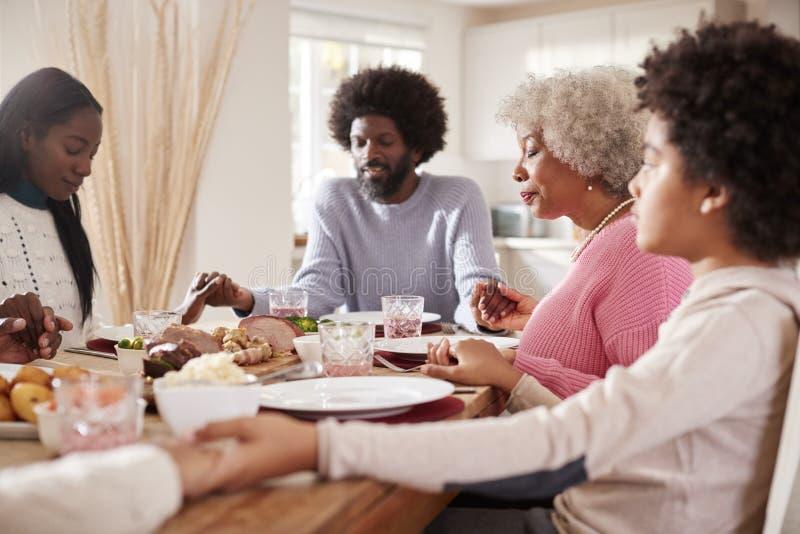 De multigeneratie mengde de holdingshanden van de rasfamilie en het zeggen van gunst alvorens hun Zondagdiner, selectieve nadruk  royalty-vrije stock foto