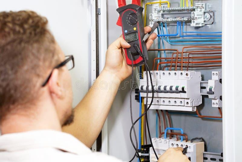 De multimeter is in handen van elektricien op achtergrond van elektroautomatiseringskabinet Een elektricien controleert het volta stock fotografie