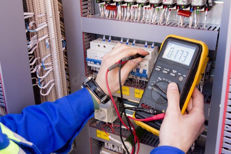 De multimeter is in handen van ingenieur in elektrokabinet Aanpassing van geautomatiseerd controlesysteem voor industrieel materi stock foto
