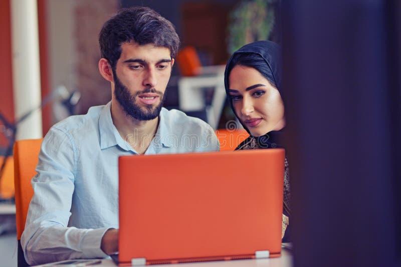 De multiraciale eigentijdse bedrijfsmensen die verbonden aan technologische apparaten zoals tablet en laptop werken royalty-vrije stock foto