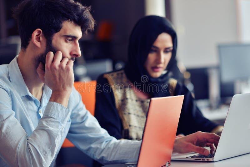 De multiraciale eigentijdse bedrijfsmensen die verbonden aan technologische apparaten zoals tablet en laptop werken royalty-vrije stock afbeelding