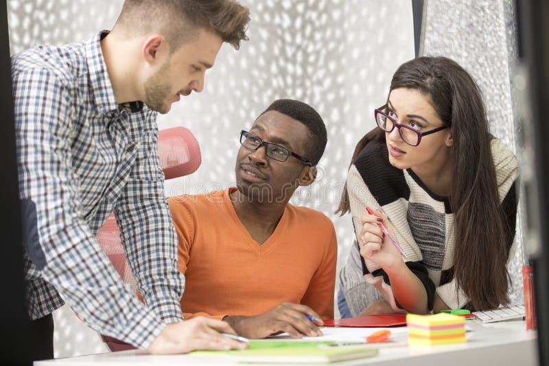 De multiraciale eigentijdse bedrijfsmensen die verbonden aan technologische apparaten zoals tablet en laptop werken stock afbeelding