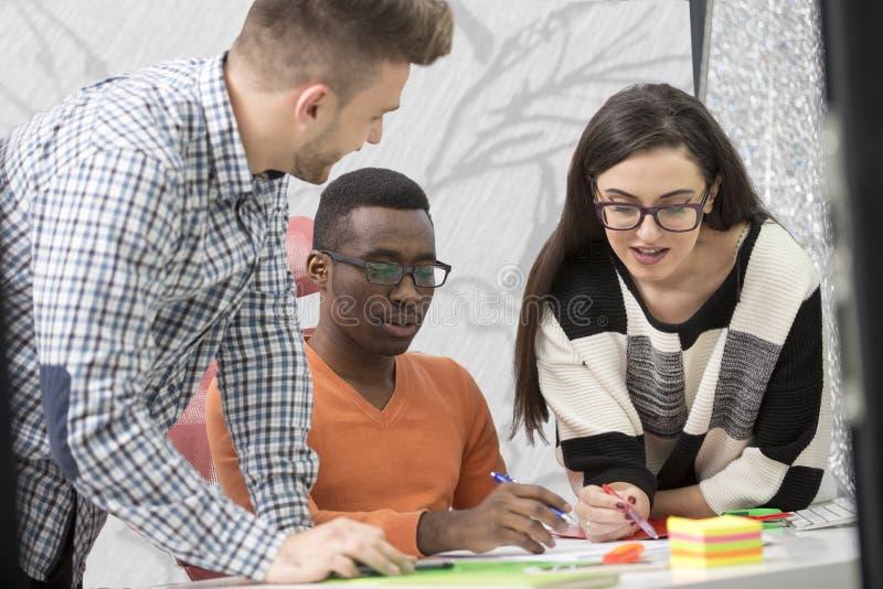 De multiraciale eigentijdse bedrijfsmensen die verbonden aan technologische apparaten zoals tablet en laptop werken stock afbeeldingen