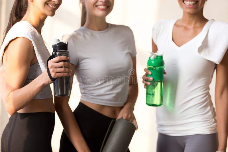 De multiraciale meisjes ontspannen drinkwater na opleiding royalty-vrije stock foto