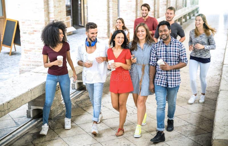De multiraciale vrienden groeperen het lopen in stadscentrum - Gelukkige kerels en meisjes die pret hebben rond oude stadsstraten stock foto
