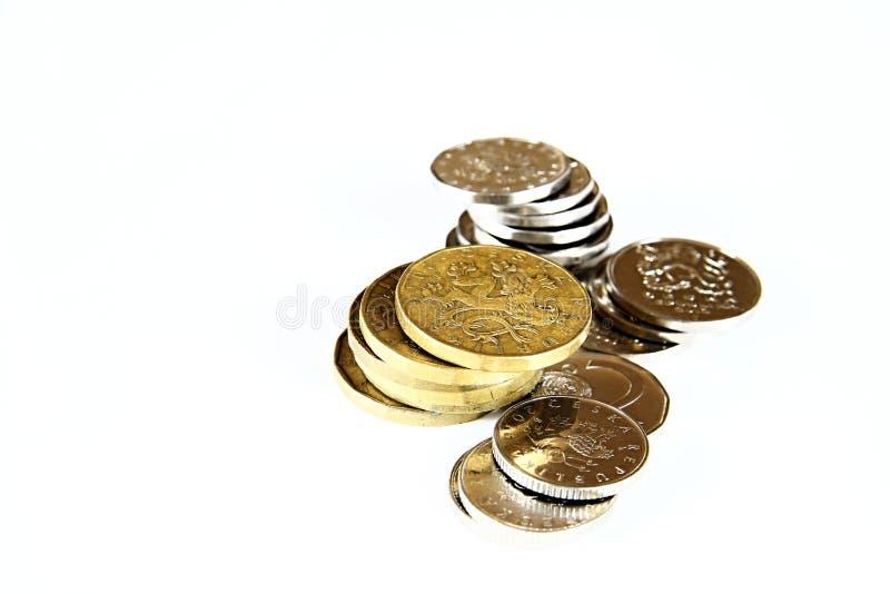 De muntstukken stapelden zich omhoog op witte oppervlakte op royalty-vrije stock afbeeldingen