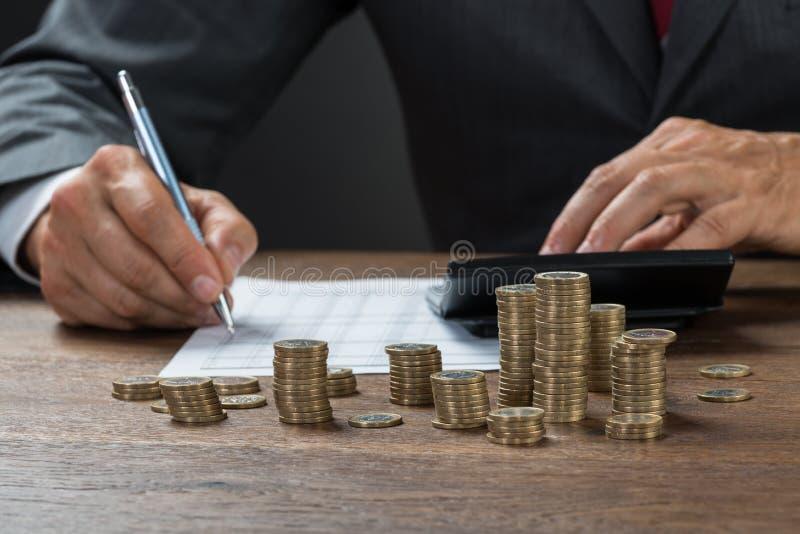 De Muntstukken van accountantscalculating profit with op Bureau royalty-vrije stock foto