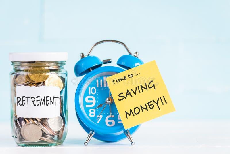 De muntstukken van de glaskruik en wekker met tijd aan besparingsgeld stock foto's