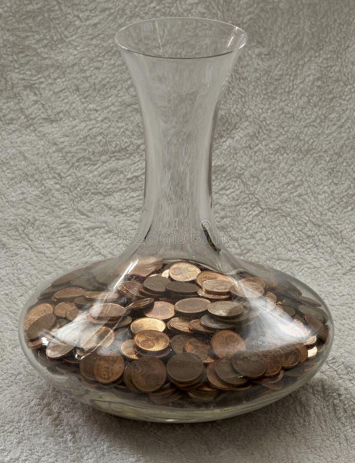 De muntstukken van het kopergeld in glasvaas stock foto