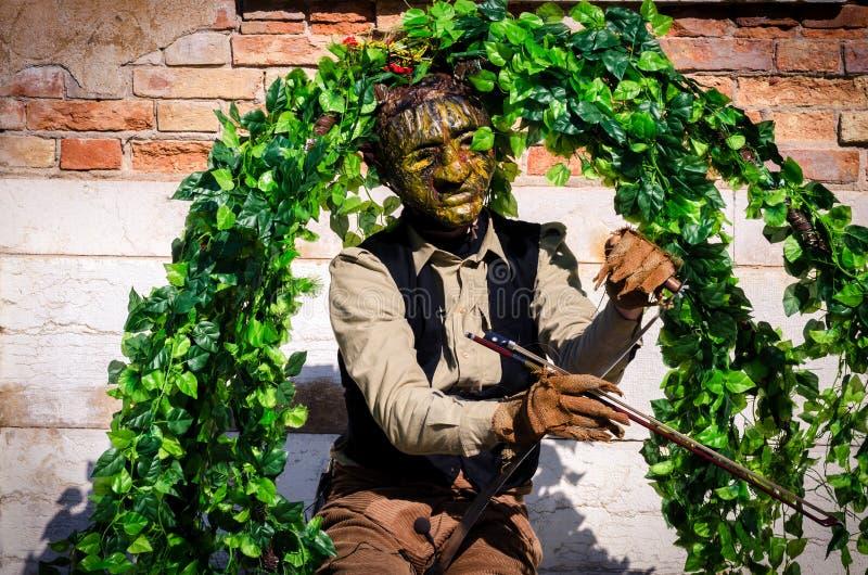 De musicus als boom wordt vermomd onderhoudt toeristen in Venetië dat stock foto's