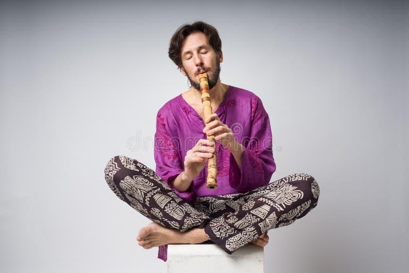 De musicus die etnische instrumenten speelt De mensenzitting in de lotusbloempositie speelt de fluit stock fotografie