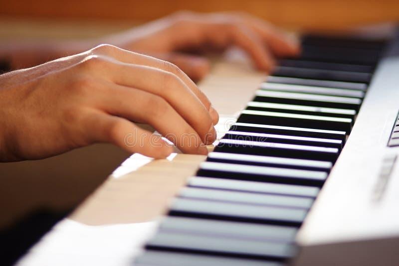 De musicus die op de sleutels van een moderne muzikale synthesizer duwen stock afbeeldingen