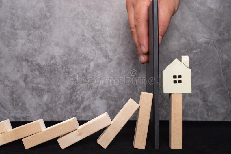 De muur houdt het huis tegen dalend neer van het concept van de dominobasis beleidsinterventie aan onroerende goederenmarkt stock afbeelding