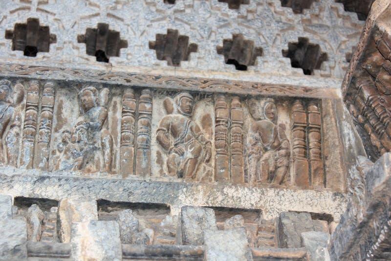 De muur van de Hoysaleswaratempel snijden die als astronauten kijken stock afbeelding