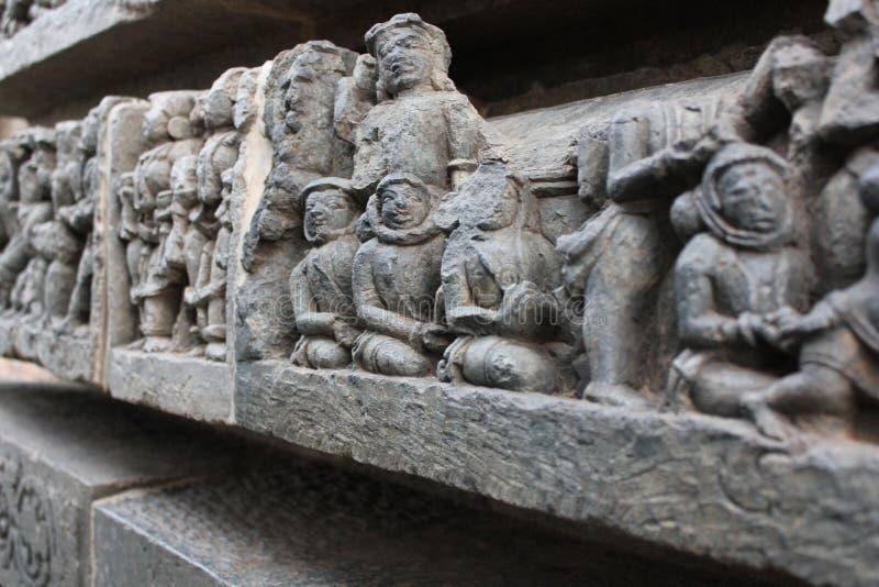De muur van de Hoysaleswaratempel snijden die als oude vreemde astronauten kijken royalty-vrije stock foto's
