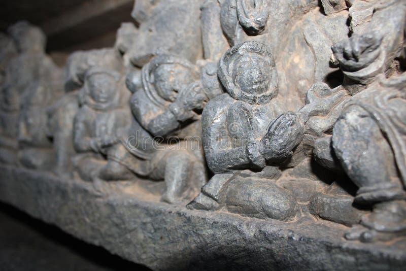 De muur van de Hoysaleswaratempel snijden die als oude vreemde astronauten met hun gadgets kijken stock afbeeldingen