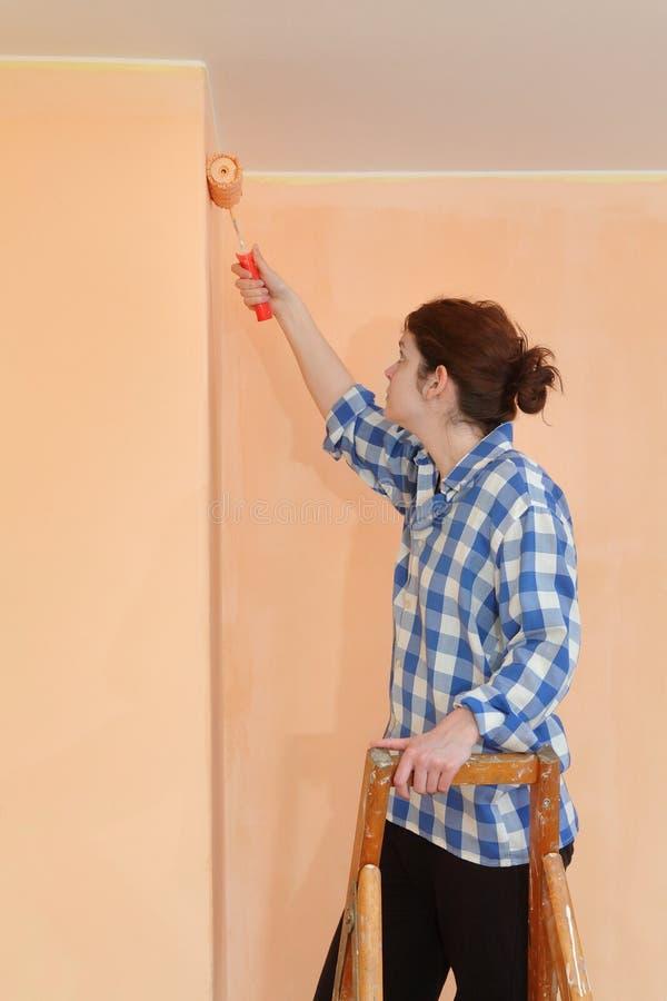 De muur van de jonge werknemerverf in een ruimte aan sinaasappel stock afbeeldingen
