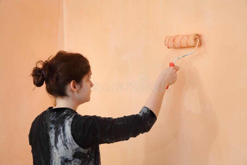 De muur van de jonge werknemerverf in een ruimte aan sinaasappel royalty-vrije stock afbeelding