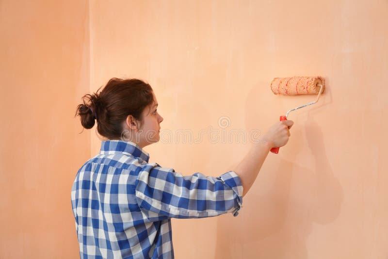 De muur van de jonge werknemerverf in een ruimte aan sinaasappel stock foto