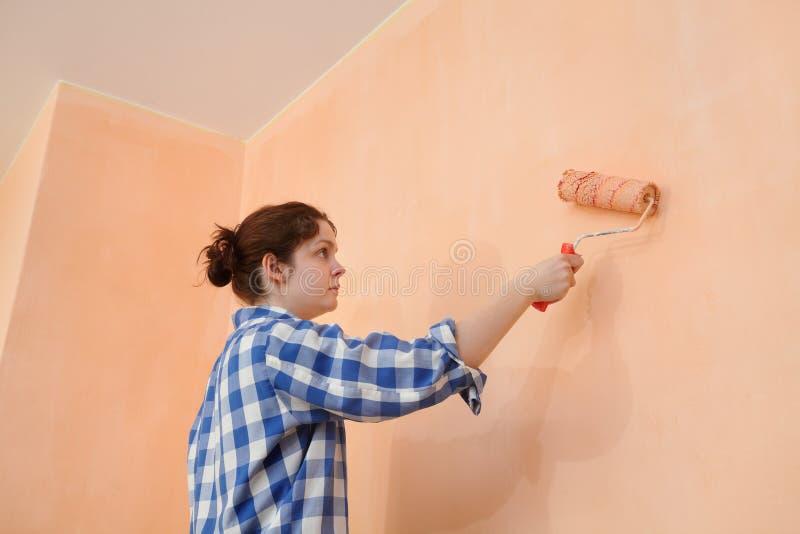 De muur van de jonge werknemerverf in een ruimte aan sinaasappel royalty-vrije stock afbeeldingen