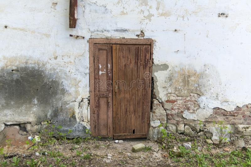 De muur van een oud huis met een deur Gevallen van pleister, bakstenen muur royalty-vrije stock foto