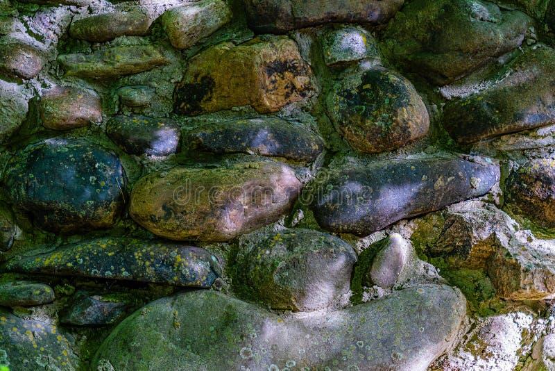 De muur van gekleurde keien maakte met cement, sporen vast van vorm, achtergrond stock afbeelding