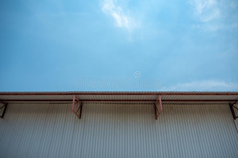 De muur van het metaalblad en dak van pakhuis met duidelijke blauwe hemel royalty-vrije stock foto's