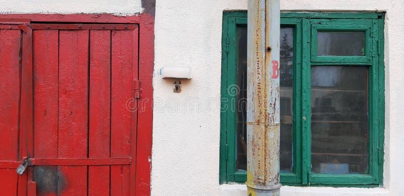 De muur van het oude huis met venster en deur stock afbeelding