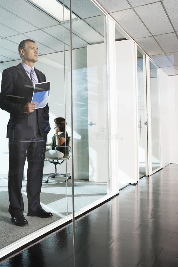 De Muur van zakenmanstanding against glass stock foto's