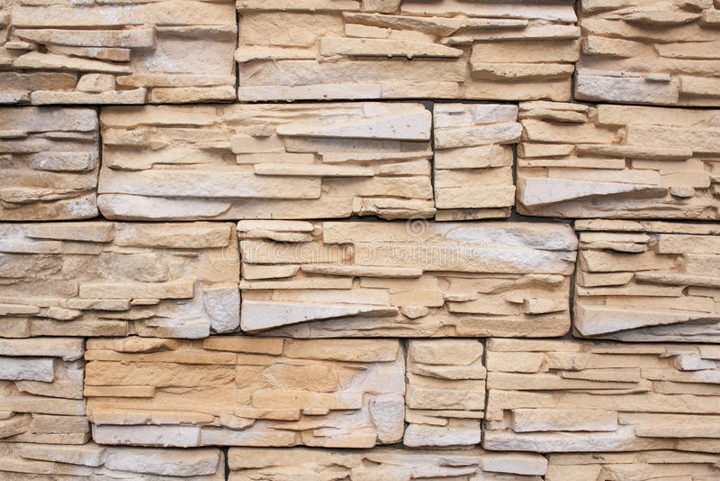 De muur wordt geconfronteerd met tegels van zandsteen stock afbeelding