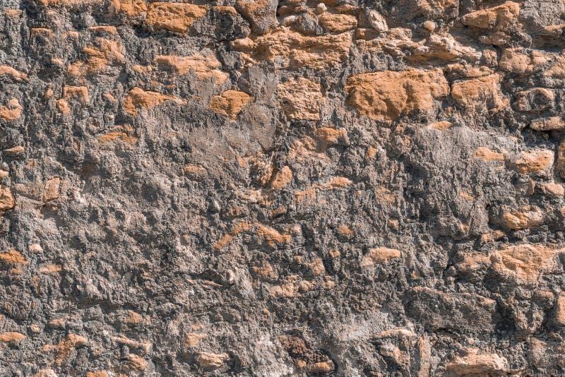De muur wordt gemaakt van ongelijk natuursteen en cement stock afbeeldingen