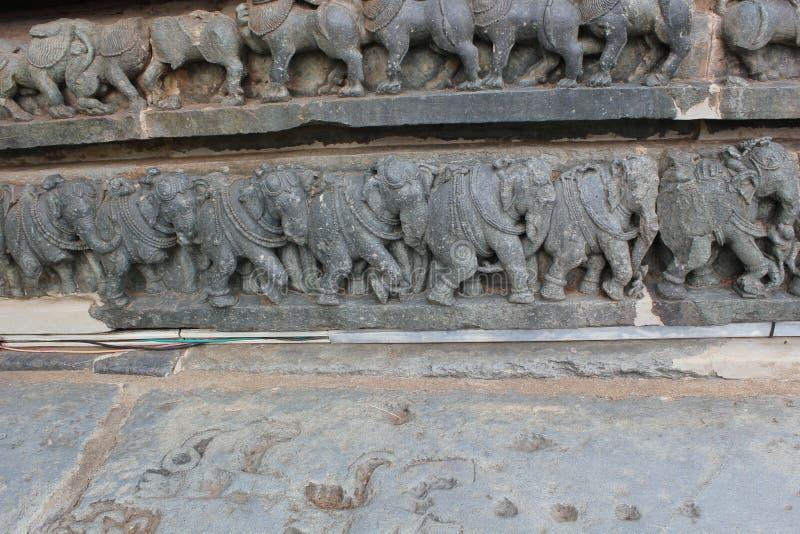 De muurgravure van de Hoysaleswaratempel van het koninklijke olifanten marcheren stock afbeeldingen
