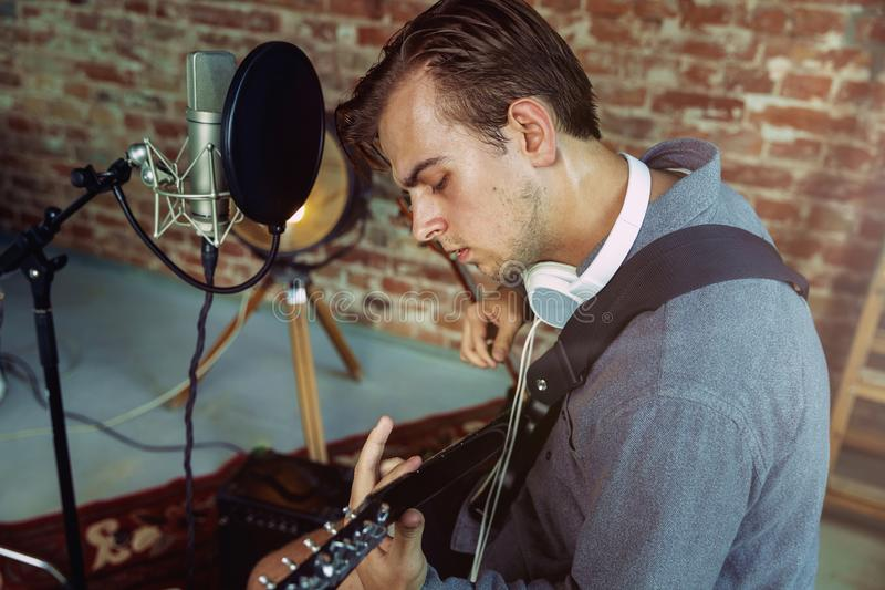 De muziek van de jonge mensenopname, het spelen gitaar en thuis het zingen stock fotografie