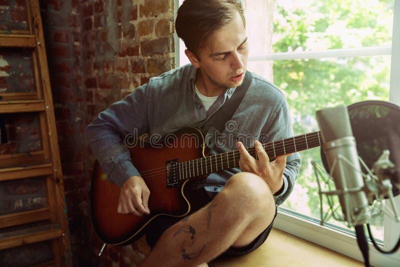 De muziek van de jonge mensenopname, het spelen gitaar en thuis het zingen royalty-vrije stock foto's