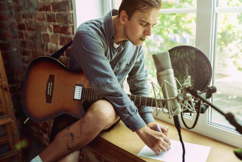 De muziek van de jonge mensenopname, het spelen gitaar en thuis het zingen stock afbeeldingen