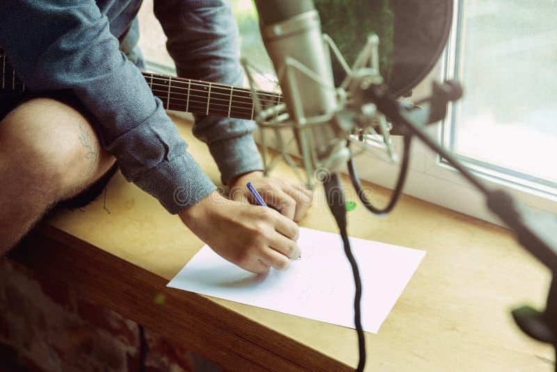 De muziek van de jonge mensenopname, het spelen gitaar en thuis het zingen stock foto