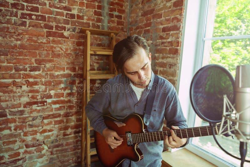 De muziek van de jonge mensenopname, het spelen gitaar en thuis het zingen stock foto's