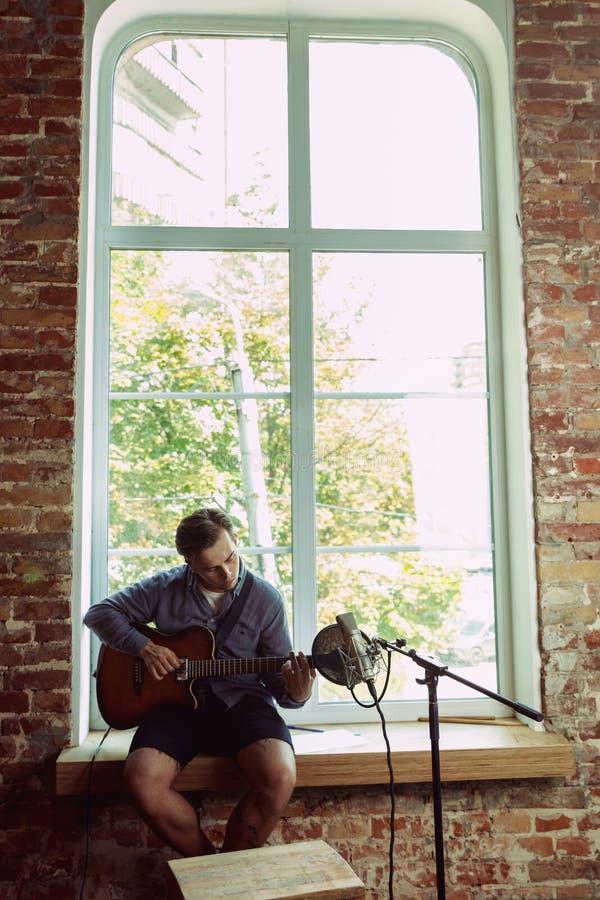 De muziek van de jonge mensenopname, het spelen gitaar en thuis het zingen stock afbeelding