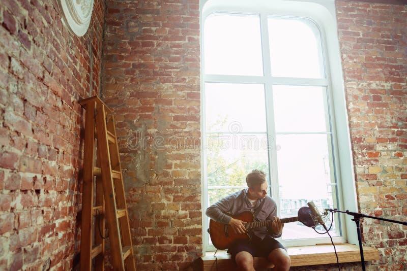 De muziek van de jonge mensenopname, het spelen gitaar en thuis het zingen royalty-vrije stock afbeeldingen