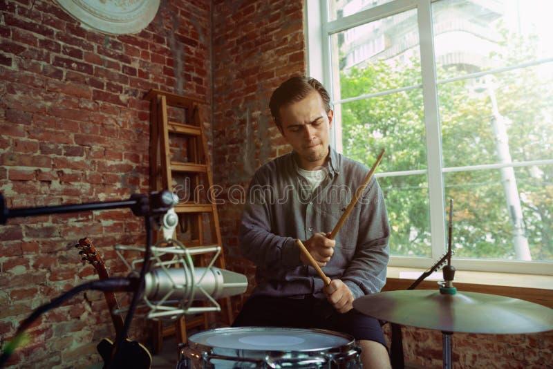 De muziek van de jonge mensenopname, het spelen trommels en thuis het zingen stock afbeelding