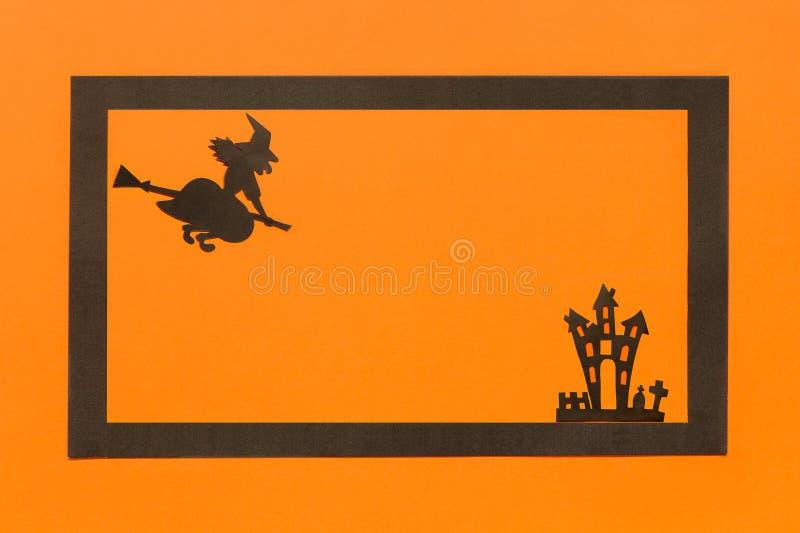 De muziek van de nacht Zwart document Heks en spookhuiskasteel en zwart kader op oranje achtergrond stock afbeeldingen