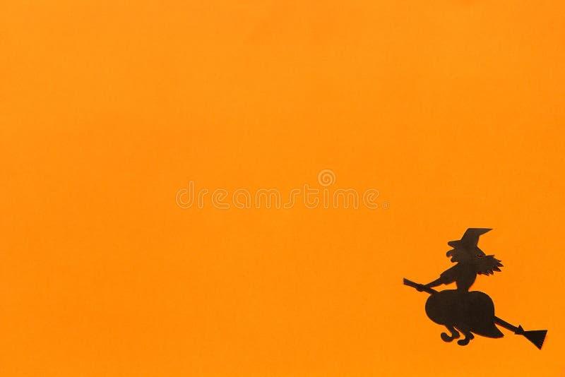 De muziek van de nacht Zwarte document heks op oranje achtergrond stock afbeeldingen