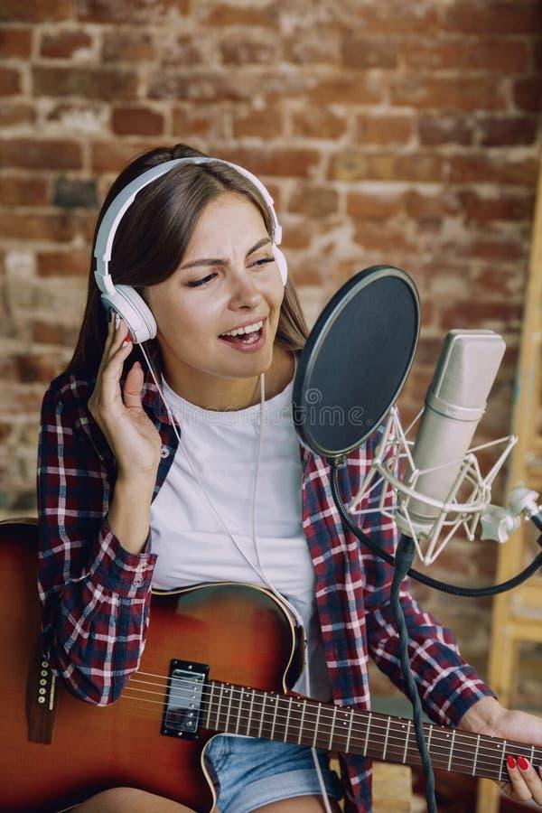 De muziek van de vrouwenopname, het spelen gitaar en thuis het zingen royalty-vrije stock fotografie