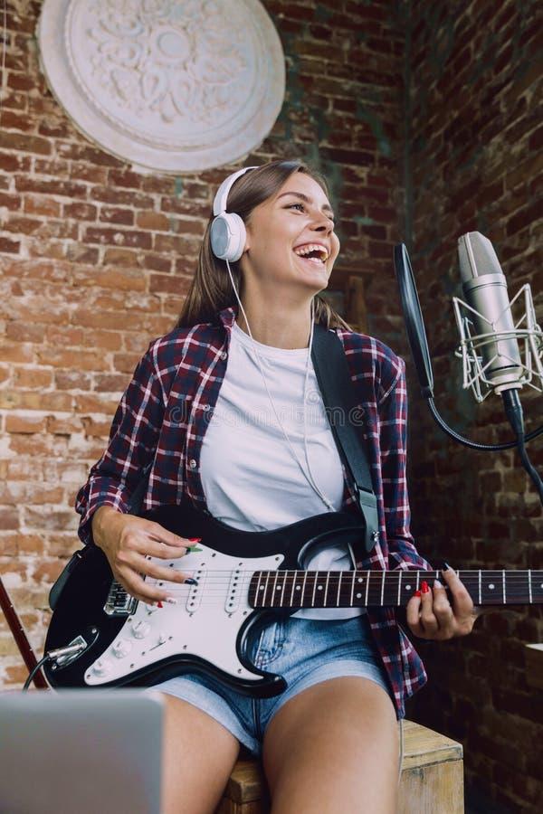 De muziek van de vrouwenopname, het spelen gitaar en thuis het zingen stock foto