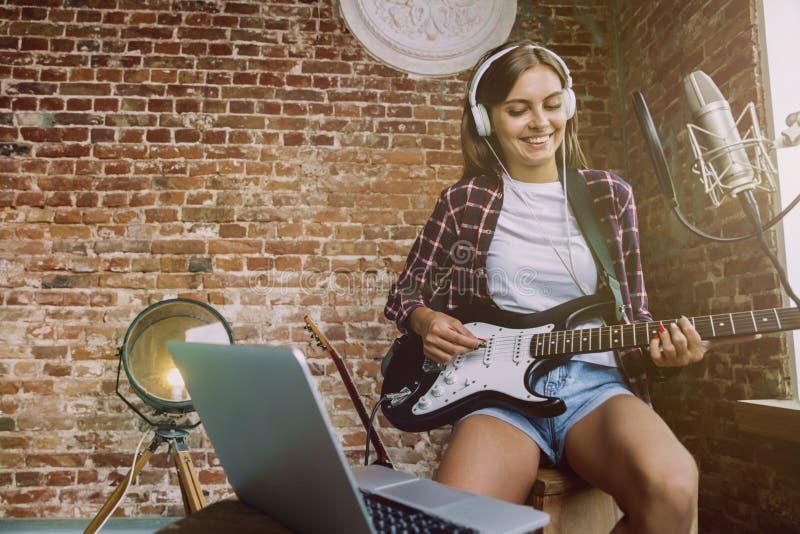 De muziek van de vrouwenopname, het spelen gitaar en thuis het zingen royalty-vrije stock foto
