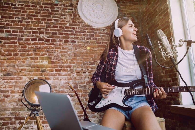 De muziek van de vrouwenopname, het spelen gitaar en thuis het zingen royalty-vrije stock afbeeldingen